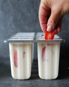 strawberries being dipped into cheesecake filled popsicle mold