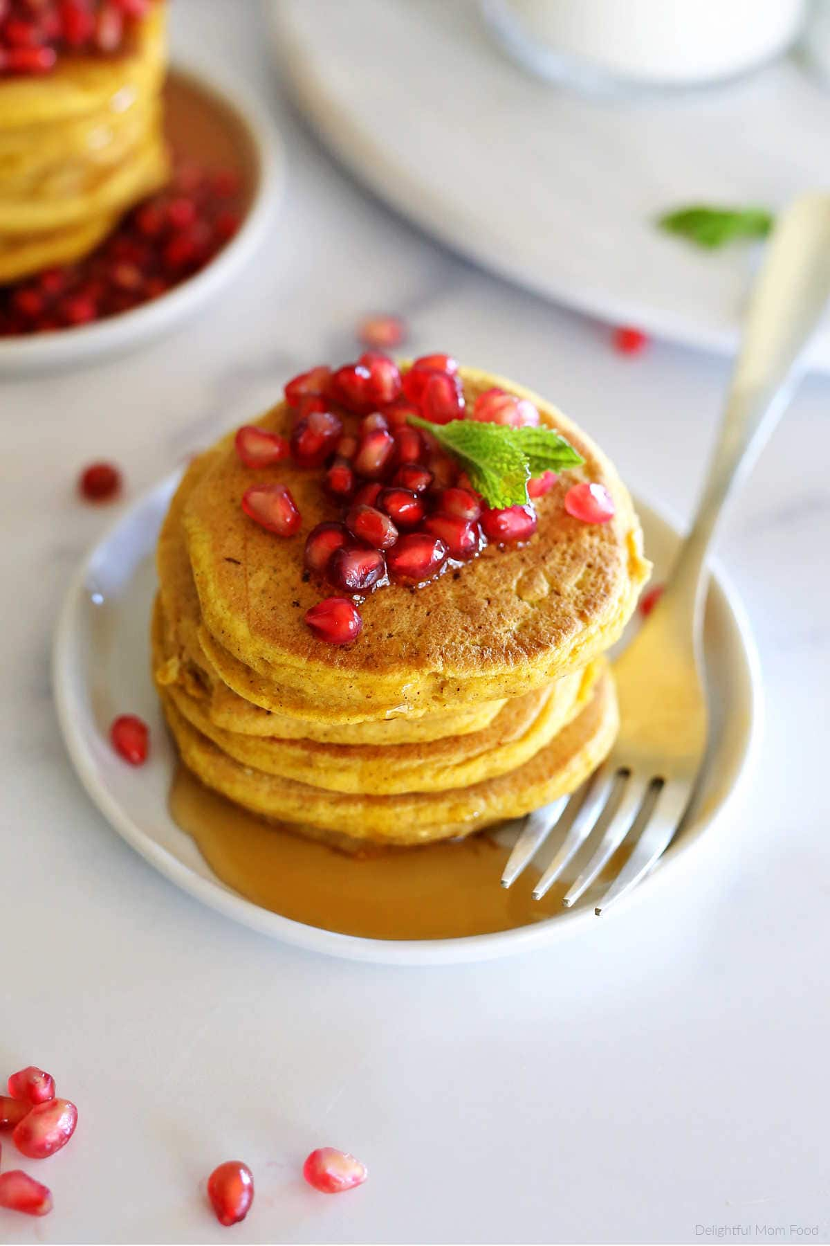gluten free pumpkin pancakes recipe with pomegranate seeds and maple syrup on a plate