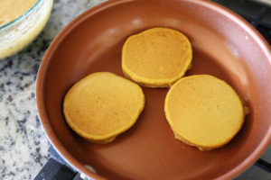 three pumpkin pancakes cooking on the stove