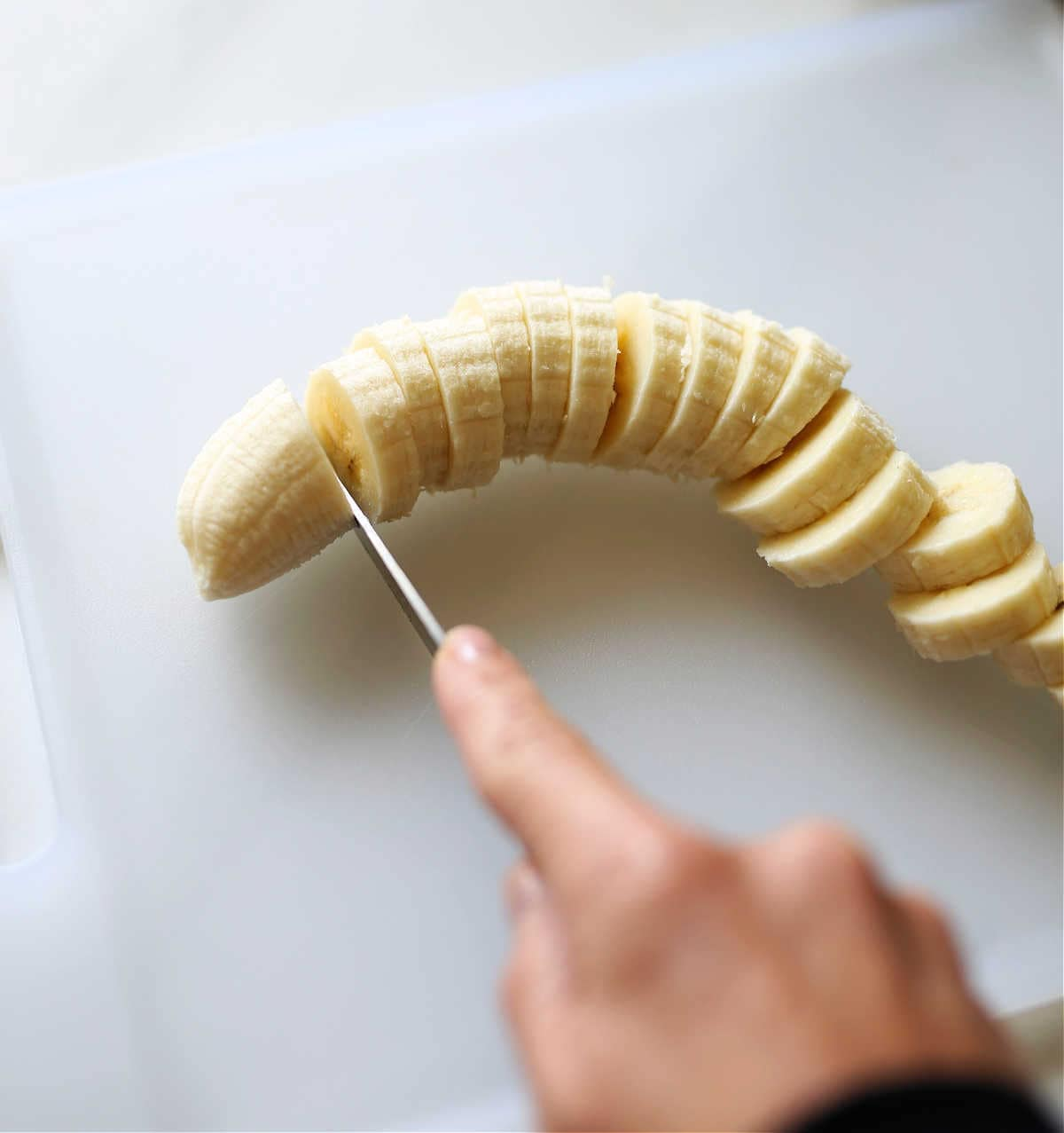 hand using a knife to slice bananas for freezing