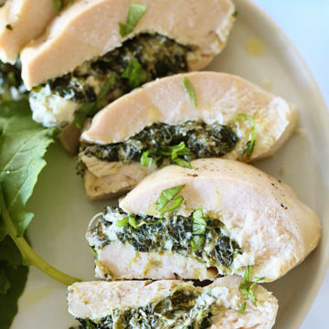 slices of goat cheese and spinach stuffed chicken recipe on a plate
